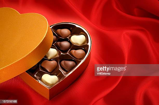 Golden chocolates box on red satin background