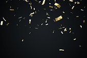Golden confetti isolated on black background. 3D rendered illustration.