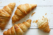 Golden croissants on rustic white wood, from above.