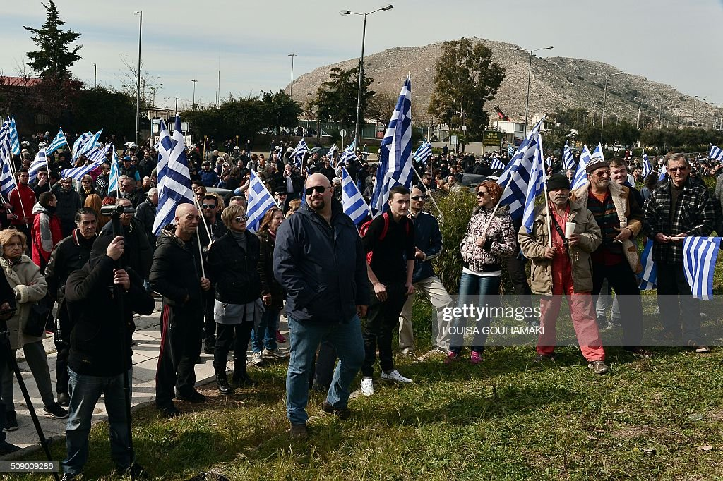 Golden Dawn party lawmaker, Ilias Panagiotaros (C) stands along far-right protesters during a rally against the construction of a new transit camp for refugees and migrants , near the port of Piraeus in Athens area on February 8, 2016. Dozens of Greek riot police have been deployed for rally organized by the far right Golden Dawn party against plans to build a new transit camp as pro-migrants groups staged a counter-demonstration near the site. / AFP / LOUISA GOULIAMAKI