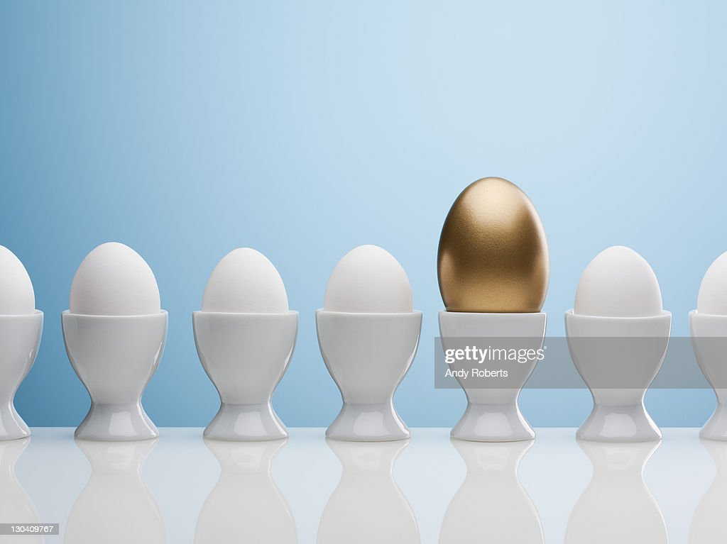 Golden egg in egg cup : Stock Photo
