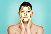 Beauty portrait of 50 year old woman with gold liguid face mask.