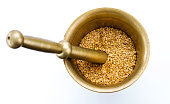 Golden flax seeds inside bronze mortar closeup isolated