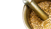Golden flax seeds inside bronze mortar closeup with copy-space