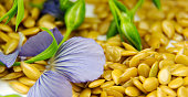 Golden flax seeds with blue flower petals closeup