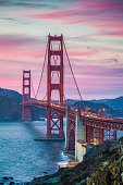 Classic panorama view of famous Golden Gate Bridge seen from scenic Baker Beach in beautiful post sunset twilight with magenta sky and clouds at dusk in summer, San Francisco, California, USA