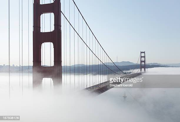 Golden Gate Bridge shrouded in fog, sailboat under the span