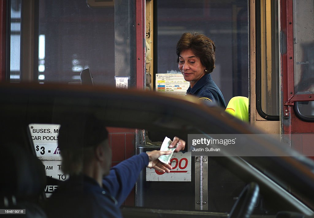 A Golden Gate Bridge toll collector receives payment from a motorist during the morning commute on March 25, 2013 in San Francisco, California. Workers are making last minute changes to the Golden Gate Bridge toll plaza in preparation of making the iconic bridge the first major toll bridge in the nation to go to all electronic tollbooths. The entire staff of full time toll collectors will be replaced by the automated booths starting on March 27.