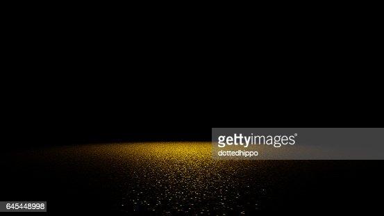 golden glitter on a flat surface lit by a bright spotlight : Foto stock