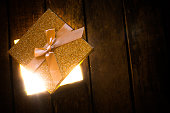 an open glowing gift box on wooden floor