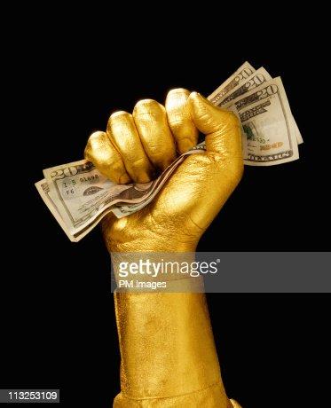 Golden hand clutching money : Stock Photo