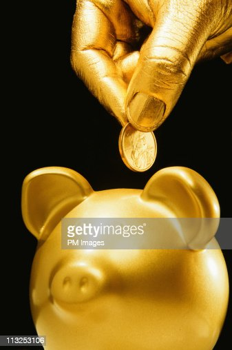 Golden hand, coin and piggy bank : Stock Photo