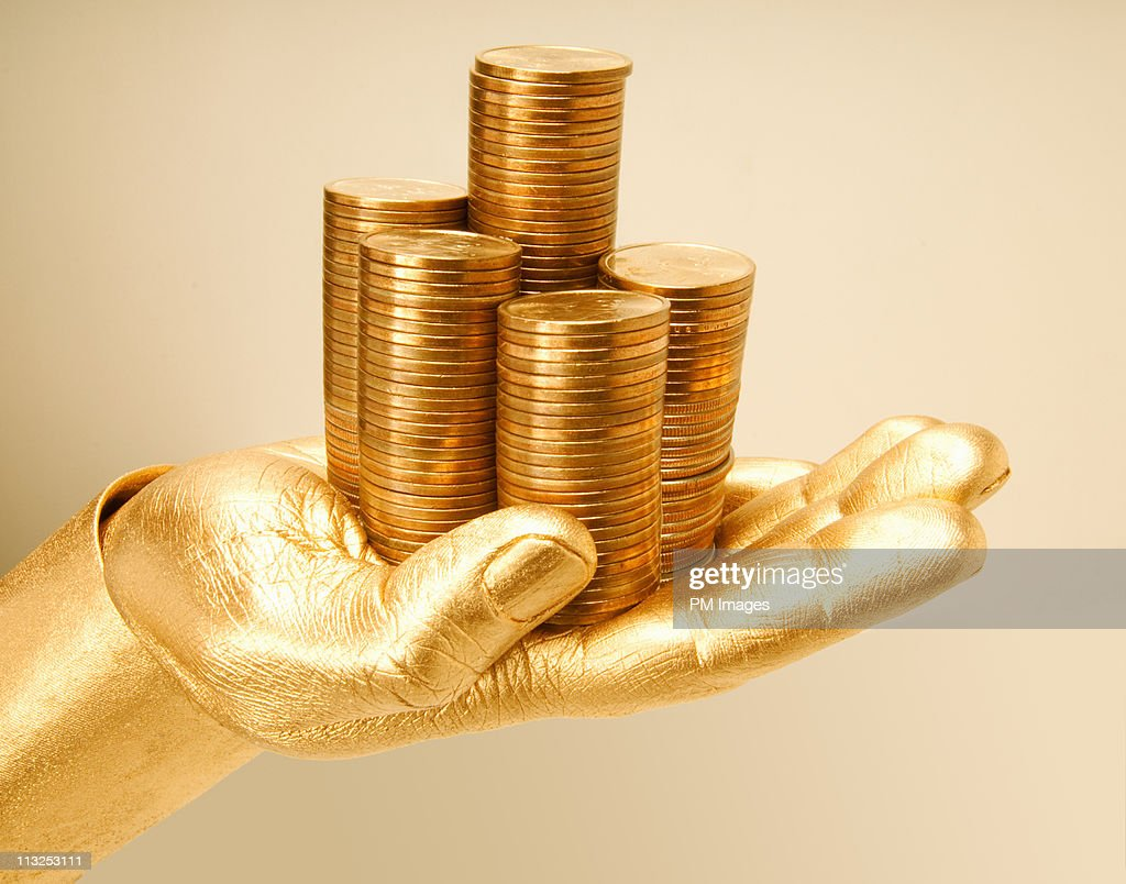 Golden hand holding stack of golden coins : Stock Photo