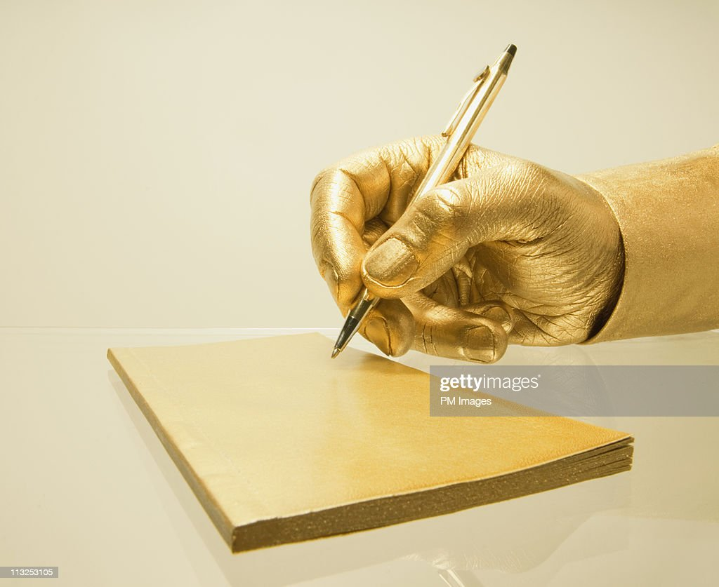 Golden hand signing check : Stock Photo