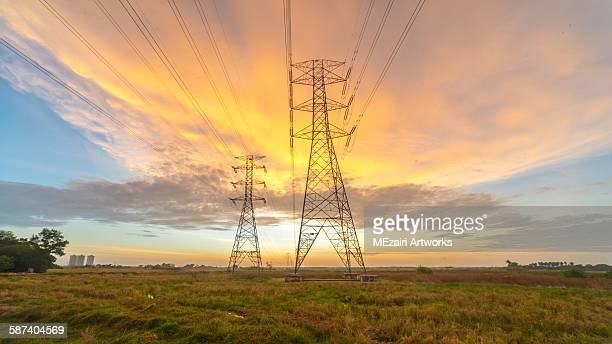 Golden hour sunset and power lines towers