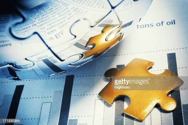 Golden jigsaw piece on financial page