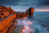 The last rays of a golden sun illuminate Pulpit Rock on the Dorset Coast, UK