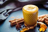 Trendy dirnk called golden milk, turmeric latte or golden latte made of tumeric and vegan organic almond milk