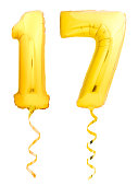 Golden number 17 seventeen made of inflatable balloon with golden ribbon isolated on white background