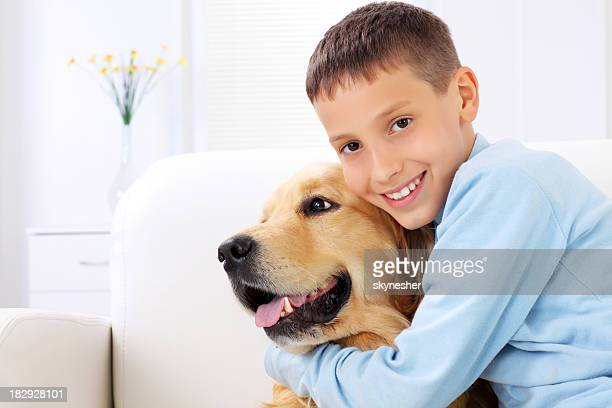 Golden Retriever in the embrace of a young boy.