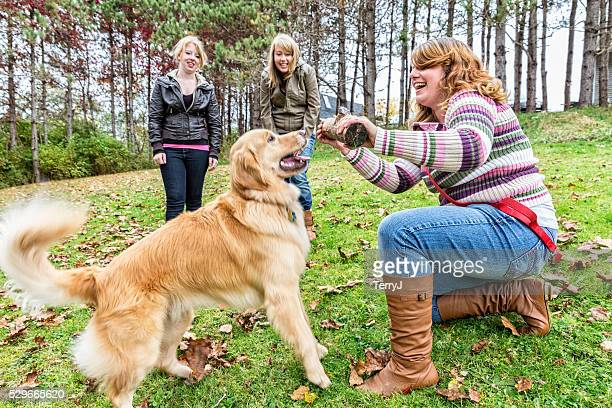 Golden Retriever Playing Outdoors with Teenagers