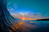 A wave reflects the sunset creating a golden road down the length of the wave.