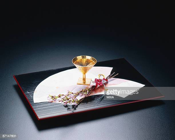 Golden sake cup on a tray