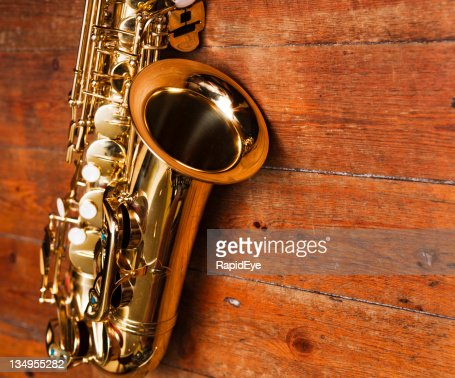Golden sax against heavily grained wood