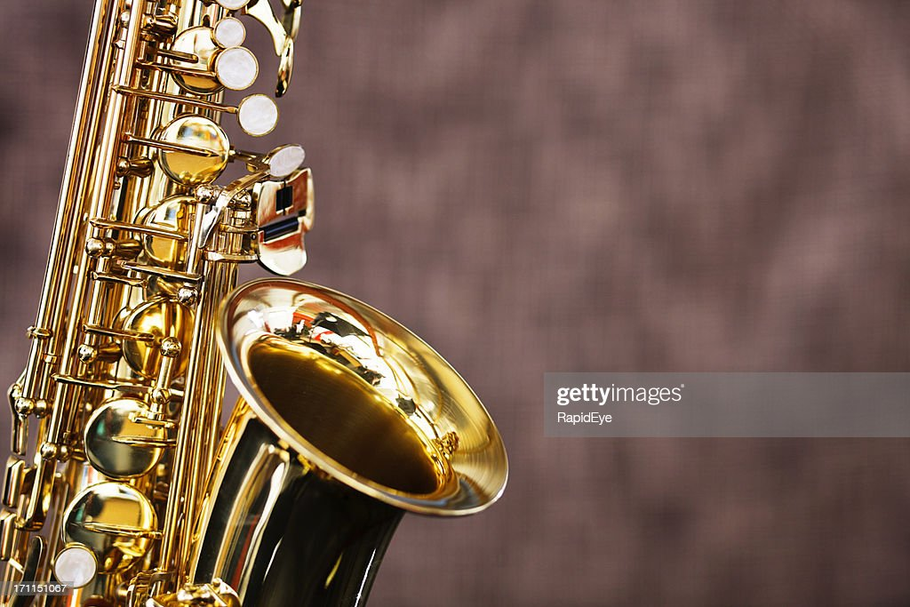 Golden saxophone shines against a dark out-of-focus background : Stock Photo