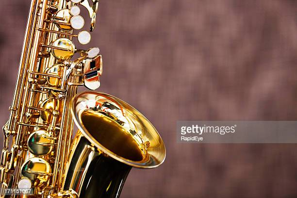 Golden saxophone shines against a dark out-of-focus background