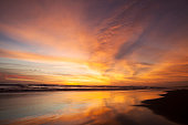 Beautiful scenery at sunset time on the tropical beach with orange color reflection of sky