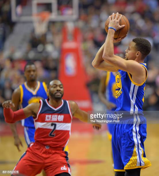 Golden State guard Stephen Curry right scores a 3 pointer over Washington guard John Wall during the Golden State Warriors defeat of the Washington...