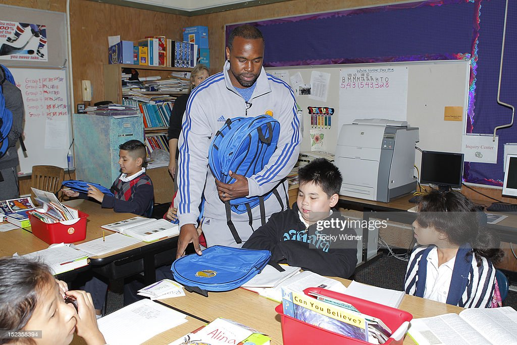 Golden State Warriors Assistant Coach Kris Weems distributes backpacks to students at Garfield Elementary on September 17, 2012 in Oakland, California.