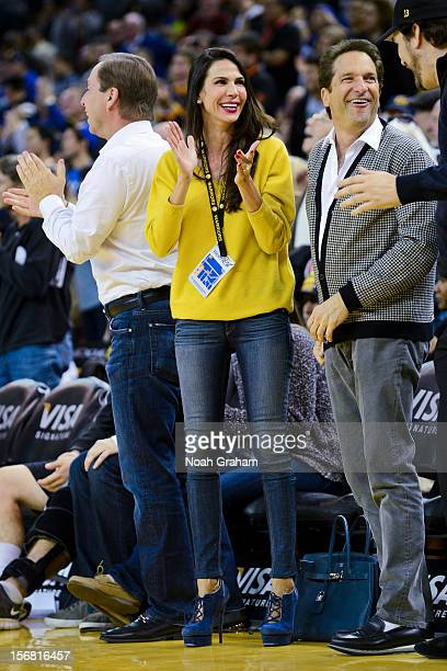 Golden State Warriors coowners Joe Lacob left and Peter Guber right along with Lacob's fiancee Nicole Curran cheer on the team during a game against...