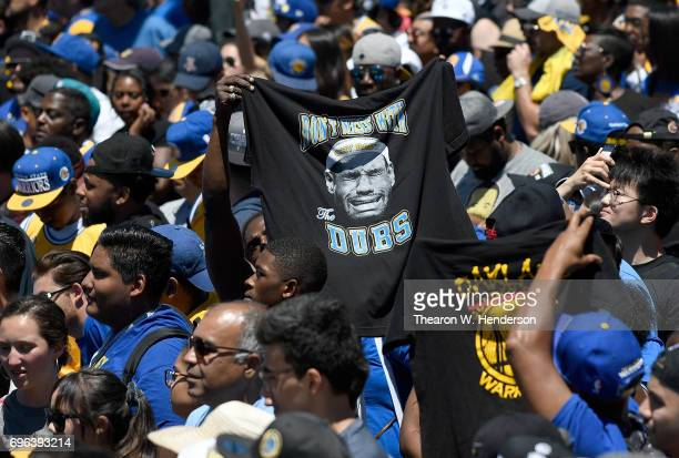 Golden State Warriors fans holding up a tshirt with LeBron James of the Cleveland Cavaliers picture on that reads 'cry baby' and 'Don't Mess With The...