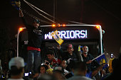 Golden State Warriors fans stand on a bus as they celebrate their team's 2015 NBA Finals win on June 16 2015 in Oakland California This is the first...