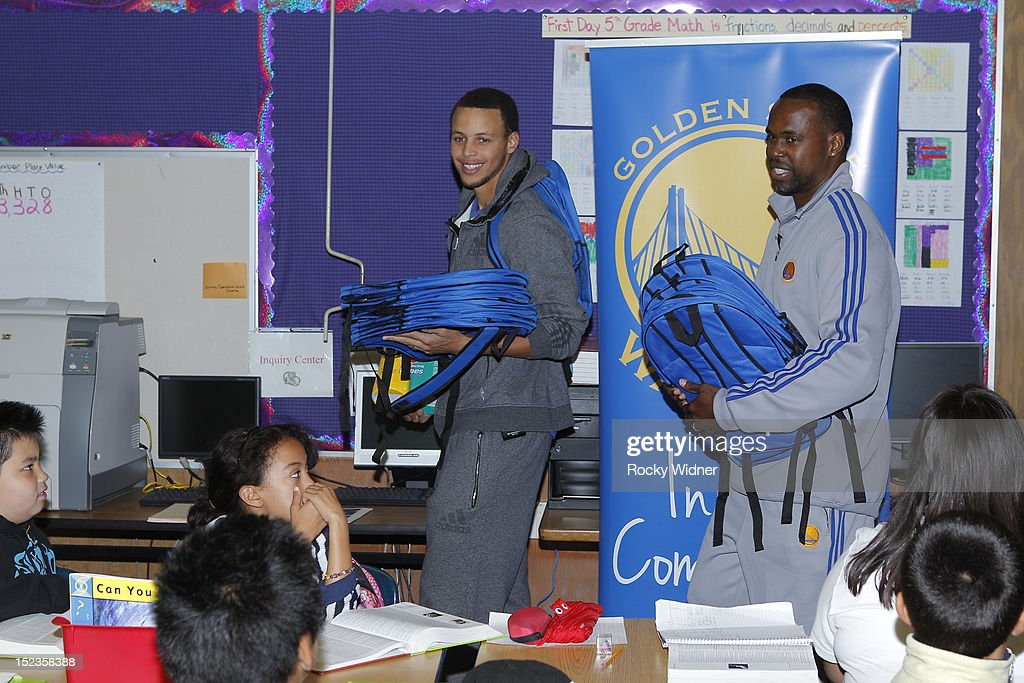 Golden State Warriors guard Stephen Curry and Assistant Coach Kris Weems distribute backpacks to students at Garfield Elementary on September 17, 2012 in Oakland, California.