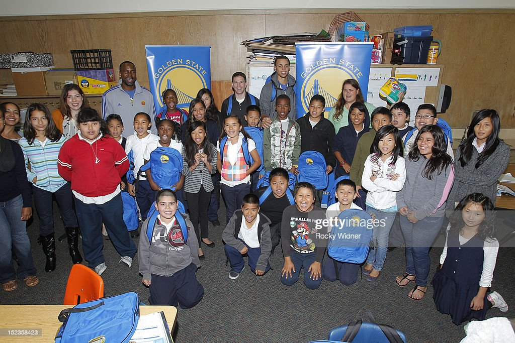 Golden State Warriors guard Stephen Curry and Assistant Coaches Darren Erman and Kris Weems pose with students at Garfield Elementary on September 17, 2012 in Oakland, California.