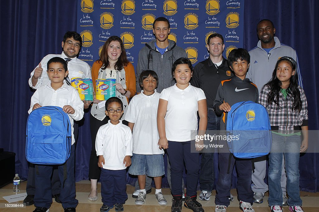 Golden State Warriors guard Stephen Curry and Assistant Coaches Darren Erman and Kris Weems pose with students and staff members at Garfield Elementary on September 17, 2012 in Oakland, California.