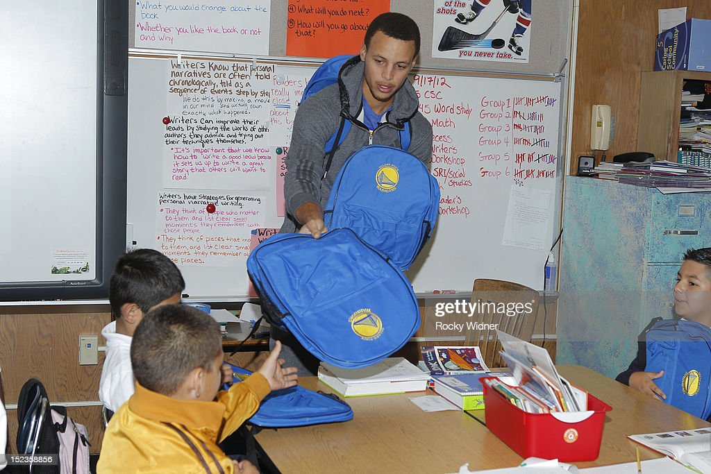 Golden State Warriors guard Stephen Curry distributes backpacks to students at Garfield Elementary on September 17, 2012 in Oakland, California.