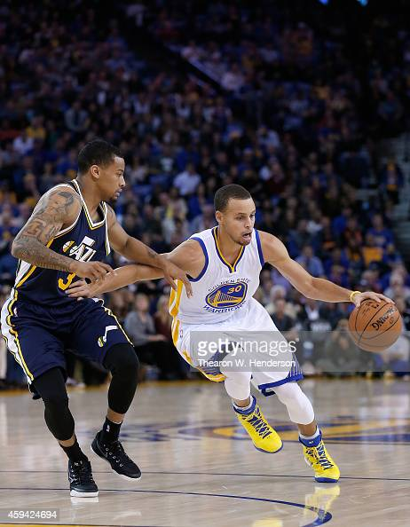 Golden State Warriors guard Stephen Curry drives on Utah Jazz guard Trey Burke at ORACLE Arena on November 21 2014 in Oakland California