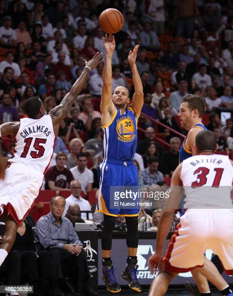 Golden State Warriors guard Stephen Curry shoots over Miami Heat guard Mario Chalmers during the first quarter at AmericanAirlines Arena in Miami on...