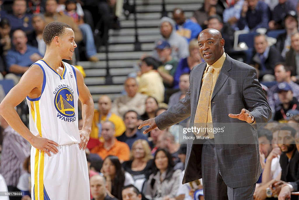 Golden State Warriors head coach Keith Smart talks with guard Stephen Curry #30 during a break in action against the Phoenix Suns on February 7, 2011 at Oracle Arena in Oakland, California.