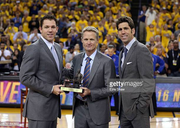 Golden State Warriors head coach Steve Kerr is given the NBA Coach of the Year Award by assistant coach Luke Walton and general manager Bob Myers...