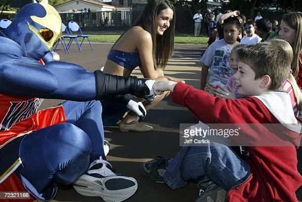 Golden State Warriors' mascot Thunder celebrates with a young fan the renovated basketball court at Eden Greenway Park on October 27 2006 in Hayward...