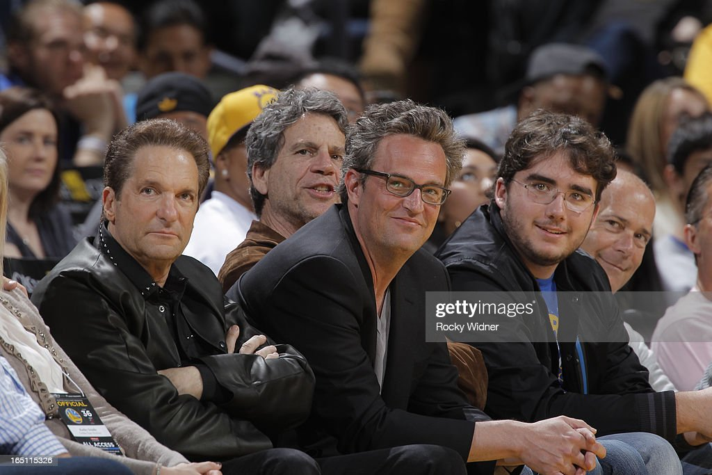 Golden State Warriors owner Peter Guber and actor Matthew Perry watch a game between the Portland Trail Blazers and the Golden State Warriors on March 30, 2013 at Oracle Arena in Oakland, California.