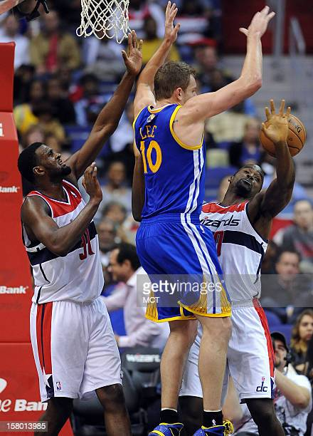 Golden State Warriors power forward David Lee loses the ball between Washington Wizards small forward Chris Singleton left and Wizards center Emeka...