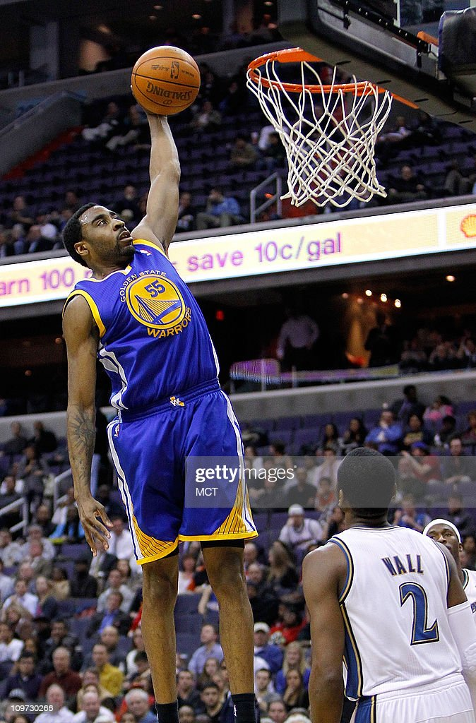 Golden State Warriors small forward Reggie Williams slam dunks as Washington Wizards point guard John Wall looks on during their game played at the...