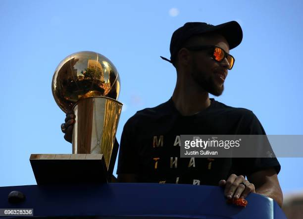 Golden State Warriors Stephen Curry holds the Larry O'Brien NBA Championship Trophy during the Warriors Victory Parade on June 15 2017 in Oakland...
