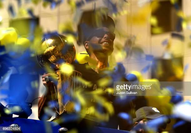 Golden State Warriors Stephen Curry is surrounded by confetti as he holds the Larry O'Brien NBA Championship Trophy during the Warriors Victory...